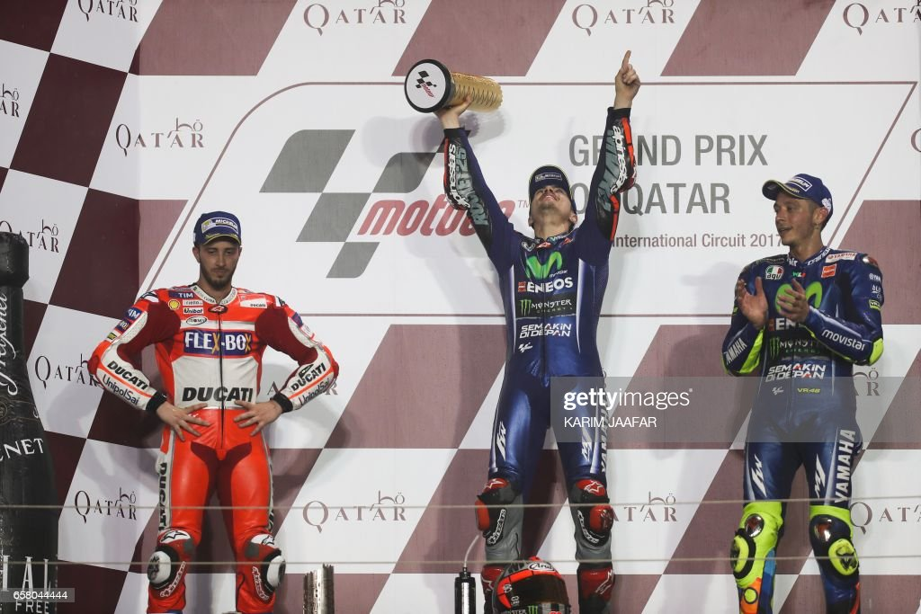 Champion Movistar Yamaha MotoGP's racers Maverick Vinales (R), teammate Valentino Rossi (C), and Ducati Team's Italian racer Andrea Dovizioso (L) celebrate on the podium after winning the 2017 Qatar MotoGP at the Losail International Circuit, north of the capital Doha on March 26, 2017. Spain's Maverick Vinales of Movistar Yamaha MotoGP won the season-opening Qatar MotoGP on March 26, 2017, shrugging off a poor start from pole position under the desert floodlights, with Italian Dovizioso coming in second on a Ducati and Rossi finishing third on a Honda. Defending world champion Marc Marquez was fourth on a Honda. / AFP PHOTO / Karim JAAFAR