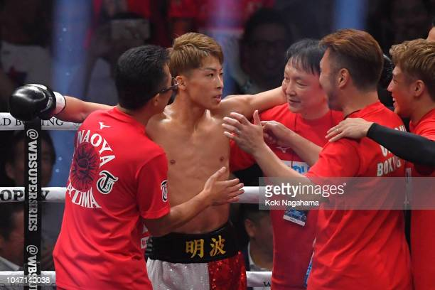 Champion Naoya Inoue of Japan celebrates with his team staff after winning against Challenger Juan Carlos Payano of the Dominican Republic during the...