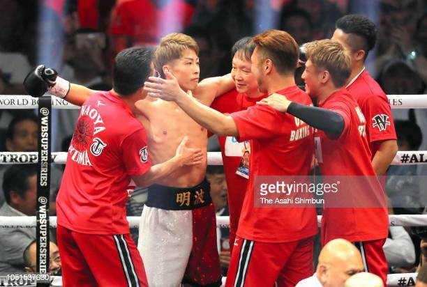 Champion Naoya Inoue of Japan celebrates with his team staffs after winning against Challenger Juan Carlos Payano of the Dominican Republic during...
