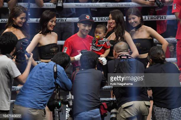 Champion Naoya Inoue of Japan poses for photographs with his baby after defeating challenger Juan Carlos Payano of the Dominican Republic during the...
