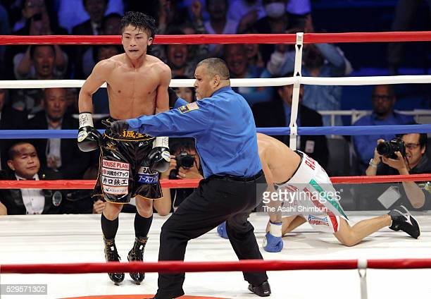 Champion Naoya Inoue of Japan reacts as he knocks down challenger David Carmona of Mexico in the 12th round during their WBO Super Flyweight Title...