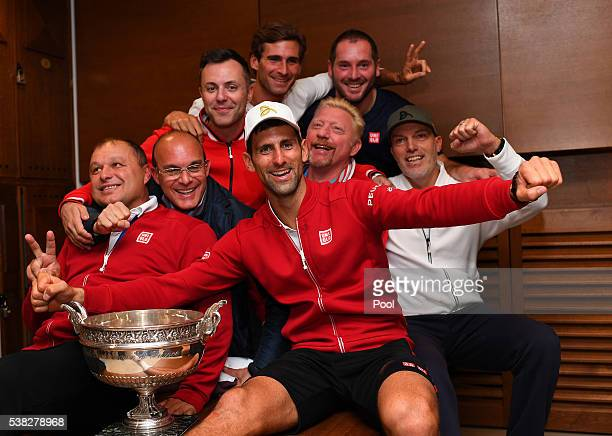 Champion Novak Djokovic of Serbia celebrates with his coaching team following his victory during the Men's Singles final match against Andy Murray of...