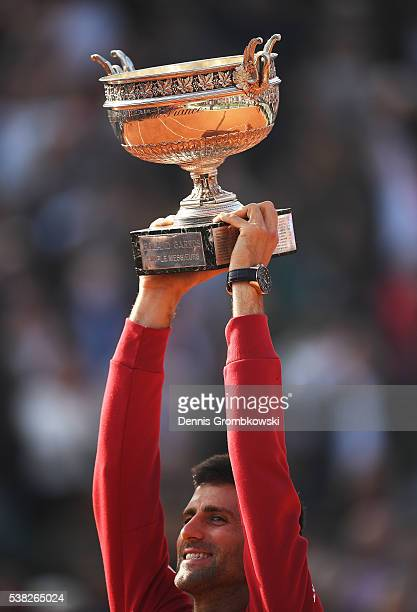 Champion Novak Djokovic of Serbia lifts the trophy following his victory during the Men's Singles final match against Andy Murray of Great Britain on...