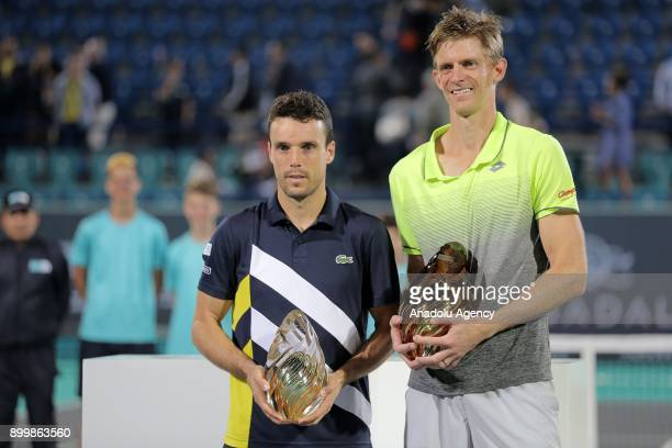 Champion of 2017 Mubadala World Tennis Championship Kevin Anderson of South Africa poses with Roberto Bautista Agut of Spain after their final match...