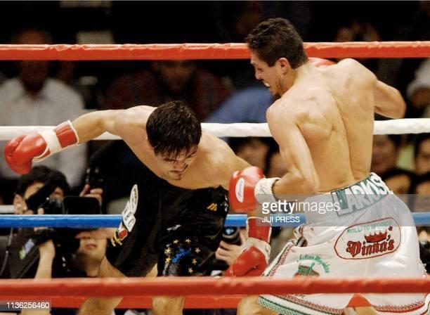 Champion Oscar Larios of Mexico punches on Japanese challenger Shigeru Nakazato during the World Boxing Council super bantamweight title match at...