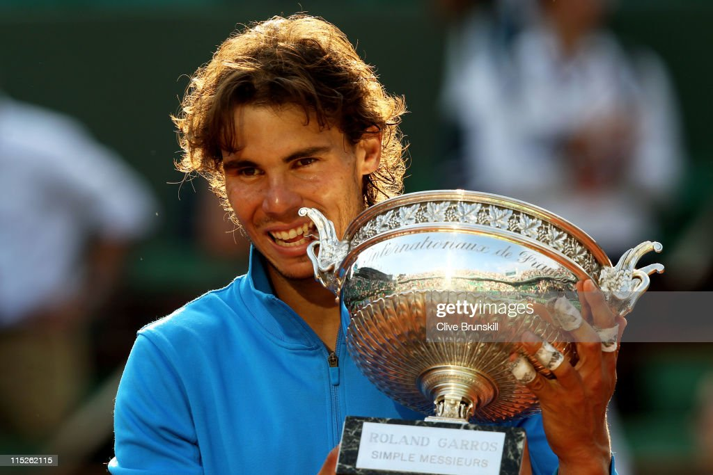 Champion Rafael Nadal of Spain bites the trophy following his record equalling sixth victory during the men's singles final match between Rafael Nadal of Spain and Roger Federer of Switzerland on day fifteen of the French Open at Roland Garros on June 5, 2011 in Paris, France.