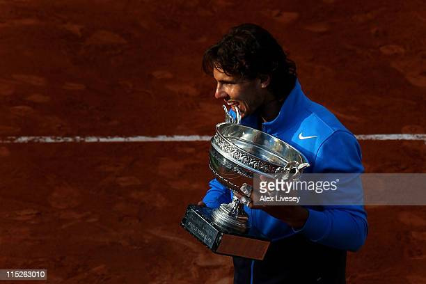 Champion Rafael Nadal of Spain bites the trophy following his record equalling sixth victory during the men's singles final match between Rafael...