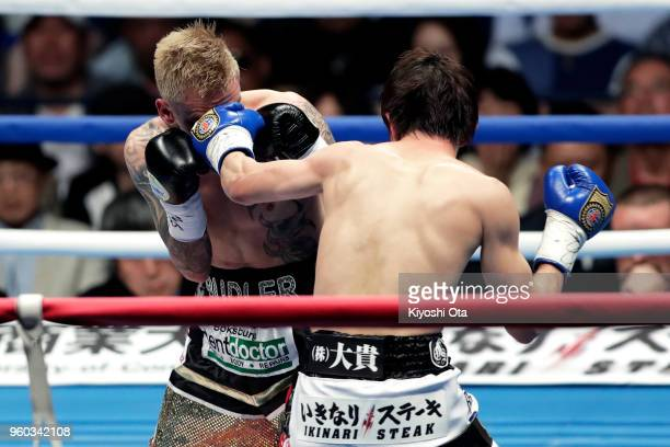 Champion Ryoichi Taguchi of Japan punches challenger Hekkie Budler of South Africa during the IBF WBA Light Flyweight Title Bout at Ota City General...