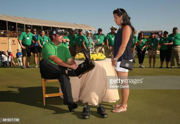 Champion Steven Bowditch receives a pair of cowboy boots as his wife Amanda looks on during the Final Round of the Valero Texas Open at TPC San...