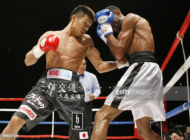 Champion Takashi Uchiyama of Japan hits his left on challenger Angel Granados of Venezuela during the WBA Super Featherweight Title Fight at Saitama...