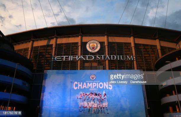 Champions banner is seen outside Etihad Stadium as Manchester City fans celebrate winning the Premier League title on May 11, 2021 in Manchester,...