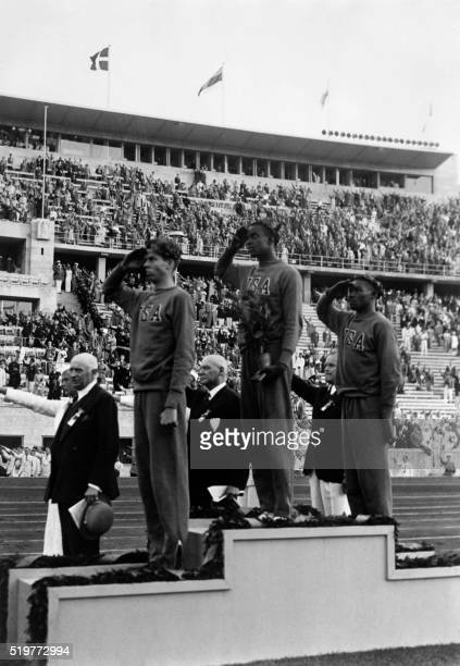 US champions Cornelius Johnson David Albritton and Delos Thurber who won the high jump gold silver and bronze medals give a military salute on the...