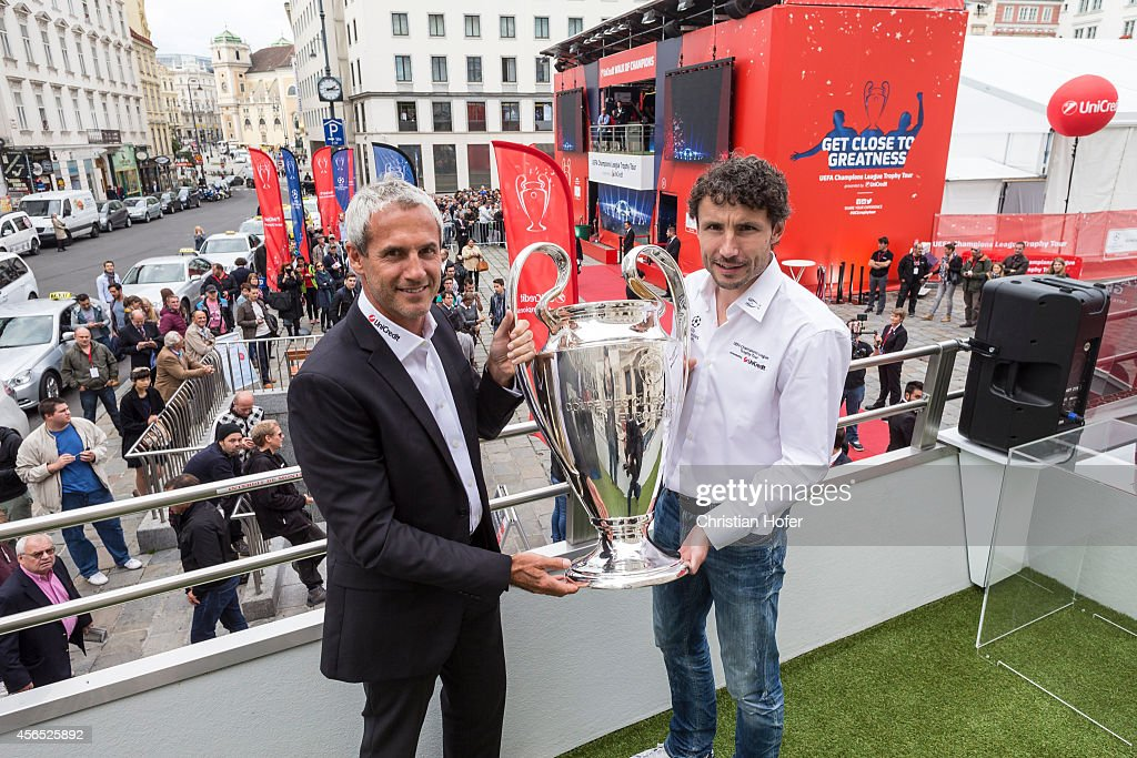 Champions League Trophy is presented to the public by UEFA Ambassador Michael Konsel (L) and UEFA Ambassador Mark van Bommel on a special bus in the streets of Vienna, Austria on October 2, 2014.