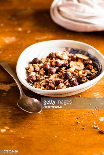 super bowl of granola or muesli with toasted oat flakes, banana chips, cashew nuts, hazelnuts on a wooden table, selective focus. food for breakfast or snack. healthy and organic food. - dörrpflaume stock-fotos und bilder