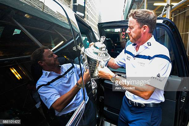 Championship winner Jimmy Walker loads his trophy into the car during a media tour on August 1, 2016 in New York City.