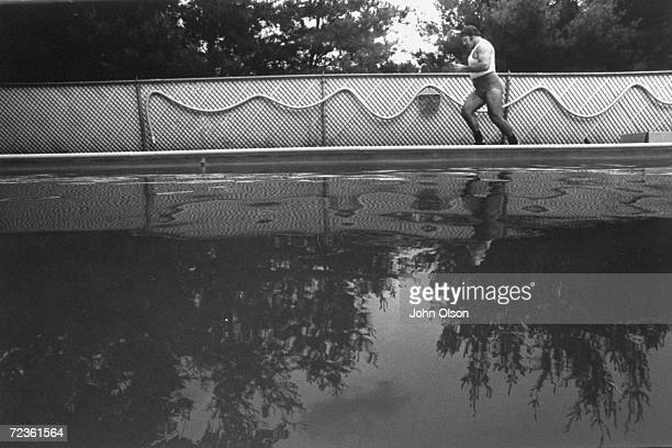 Championship wrestler Bruno Sammartino jogging around his pool as part of his daily exercise routine.
