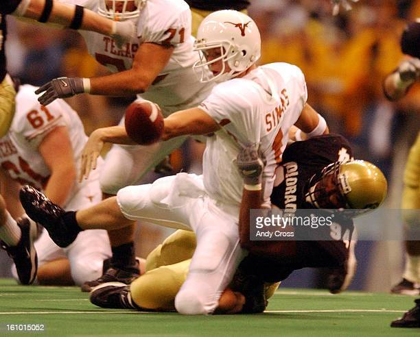 DeAndre Fluellen, #94, Colorado, pulls down Texas QB, Chris Simms, #1, as Simms fumbled, in the second quarter of play during the Big 12 championship...