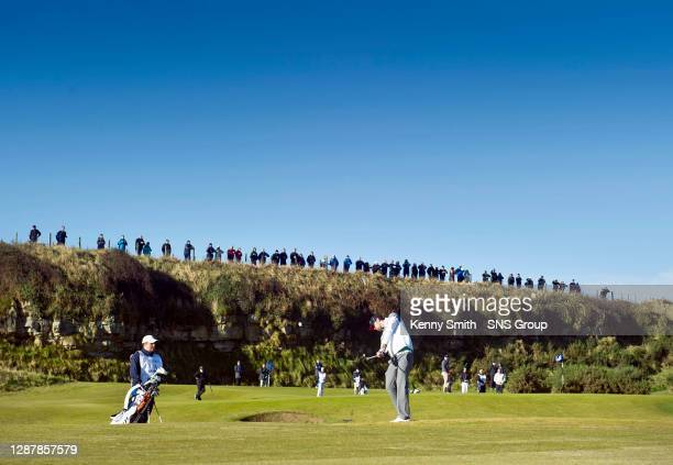 Michael Phelps plays to the 12th hole with a large gallery watching from the hillside.