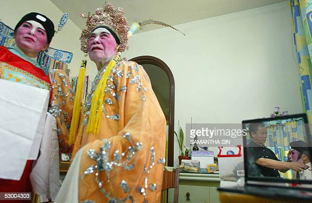 STORY AFPENTERTAINMENTHONG KONGOPERA Chan Gumto Cantonese opera performer and instructor helps a student put on a traditional costume and make up as...