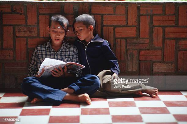 Chan Roeun reads a book to another boy at the Wat Norea Peaceful Children's Home in Battambang Much of life at the home revolves around education The...