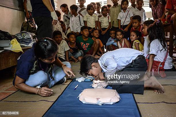 Chan Sovanna from Safety When It Matters Cambodia instructs a student how to perform CPR on a mannequin during a water safety and drowning prevention...