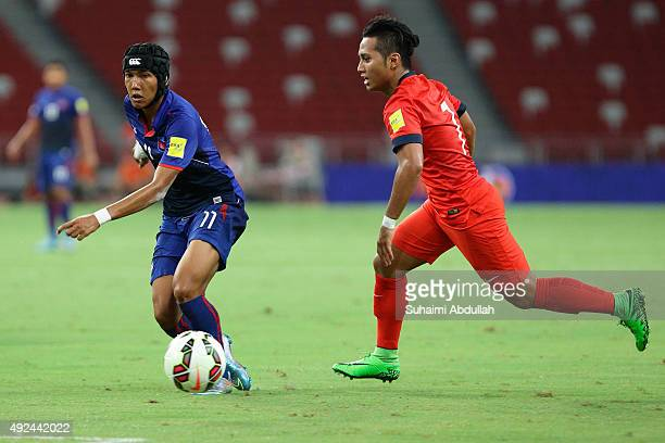 Chan Vathanaka of Cambodia dribbles past Sahil Suhaimi of Singapore during the 2018 FIFA World Cup Qualifier Group E Match between Singapore and...