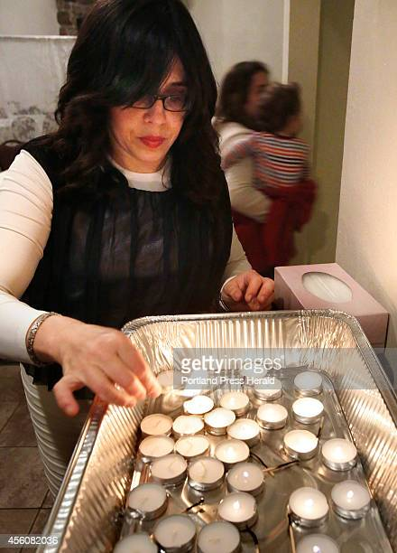 Chana Wilansky of Portland lights a candle before the start of a Rosh Hashanah service at the Italian Heritage Center in Portland on Wednesday,...