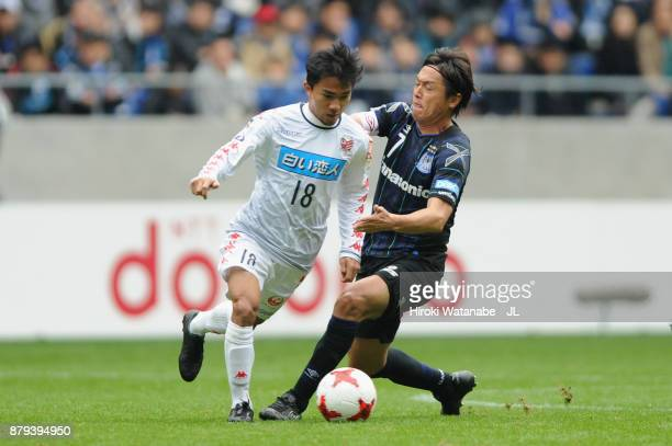 Chanathip Songkrasin of Consadole Sappporo and Yasuhito Endo of Gamba Osaka compete for the ball during the JLeague J1 match between Gamba Osaka and...