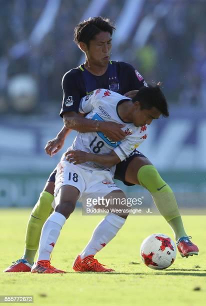 Chanathip Songkrasin of Consadole Sappporo controls the ball under pressure of Daiki Niwa of Sanfrecce Hiroshima during the JLeague J1 match between...