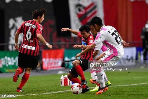 Chanathip Songkrasin of Consadole Sappporo controls the ball under pressure of Kei Ikeda of Sagan Tosu during the JLeague J1 match between Consadole...