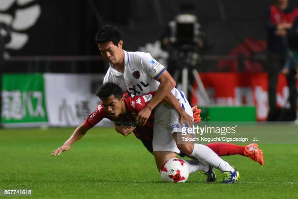 Chanathip Songkrasin of Consadole Sappporo is challenged by Yukitoshi Ito of Kashima Antlers during the JLeague J1 match between Consadole Sapporo...