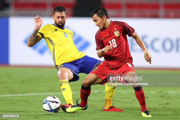 Chanathip Songkrasin of Thailand and Palun Lloyd of Gabon competes for the ball during the international friendly match between Thailand and Gabon at...