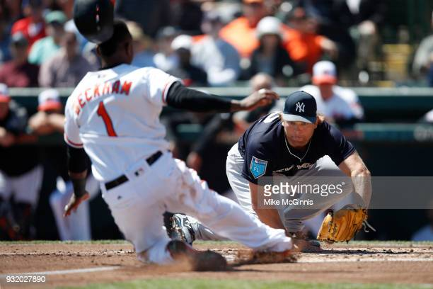 Chance Adams of the New York Yankees tags out Tim Beckham of the Baltimore Orioles during the second inning of the Spring Training game against the...