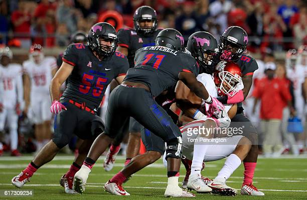 Chance Allen of the Houston Cougars carries the ball against Carlos Carroll of the Southern Methodist Mustangs, Kyran Mitchell of the Southern...