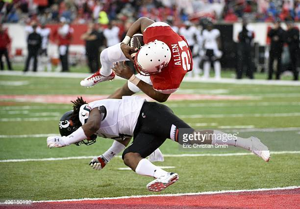 Chance Allen of the Houston Cougars jumps over Leviticus Payne of the Cincinnati Bearcats for an 11yard touchdown in the second quarter of a NCAA...
