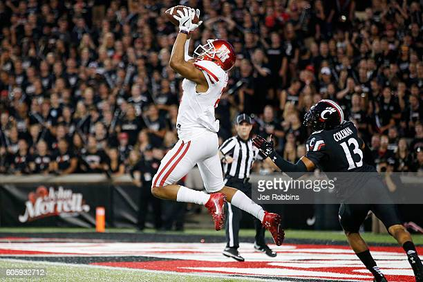 Chance Allen of the Houston Cougars leaps for a 39-yard touchdown reception against Grant Coleman of the Cincinnati Bearcats in the first half at...