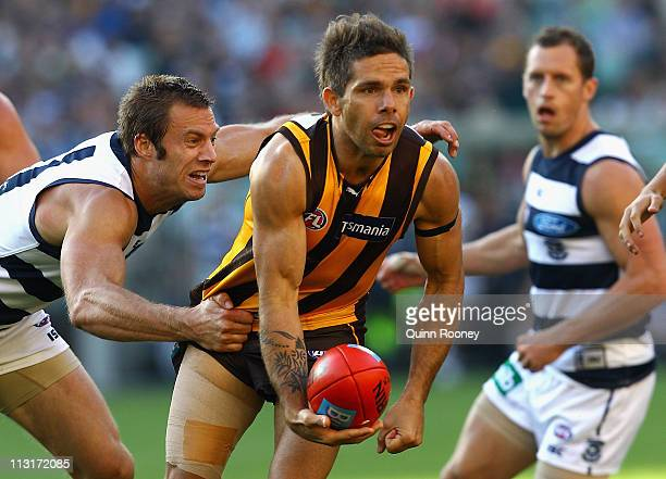 Chance Bateman of the Hawks handballs whilst being tackled by Joel Corey of the Cats during the round five AFL match between the Hawthorn Hawks and...