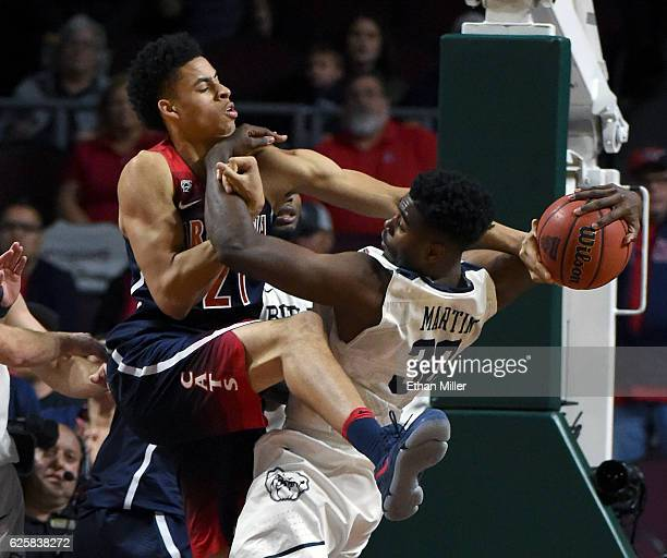 Chance Comanche of the Arizona Wildcats and Kelan Martin of the Butler Bulldogs go after a loose ball during the championship game of the 2016...