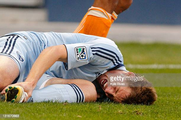 Chance Myers of the Sporting Kansas City reacts in pain after having his foot stepped on against the Houston Dynamo in the first half during the MLS...