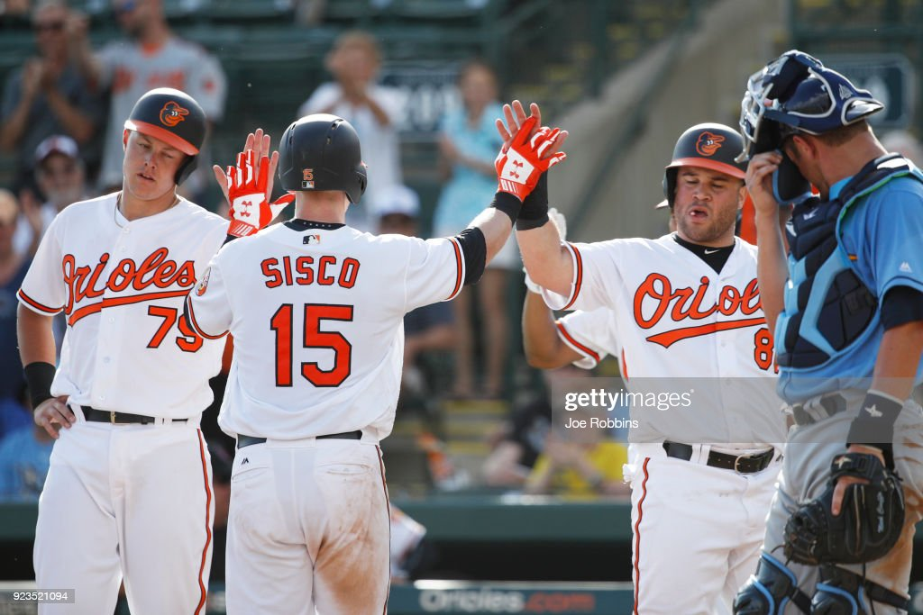 Chance Sisco #15 of the Baltimore Orioles celebrates with teammates after hitting a three-run home run against the Tampa Bay Rays in the ninth inning during a Grapefruit League spring training game at Ed Smith Stadium on February 23, 2018 in Sarasota, Florida. The Rays won 6-3.