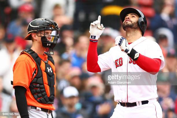 Chance Sisco of the Baltimore Orioles looks on as JD Martinez of the Boston Red Sox reacts as he crosses home plate after hitting a solo home run in...