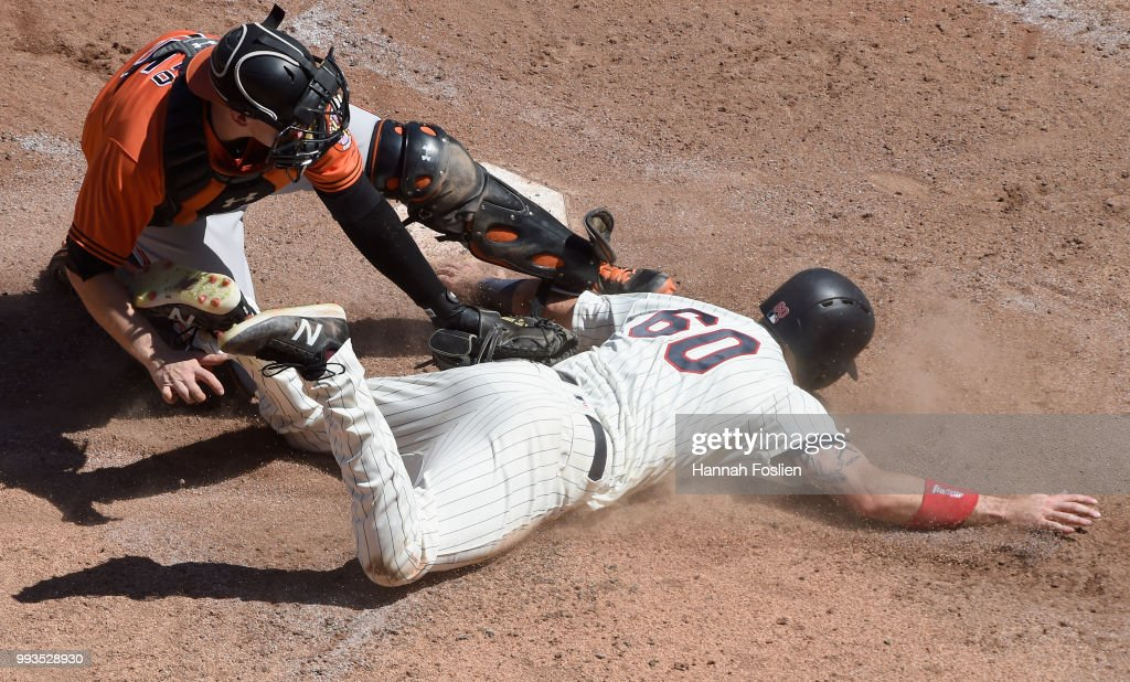 Chance Sisco #15 of the Baltimore Orioles tags out Jake Cave #60 of the Minnesota Twins at home plate during the sixth inning of the game on July 7, 2018 at Target Field in Minneapolis, Minnesota. The Twins defeated the Orioles 5-4.