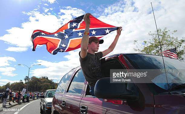 Chance White holds a confederate flag as he drives past protesters lining the street in front of the Roseburg Regional Airport on October 9 2015 in...