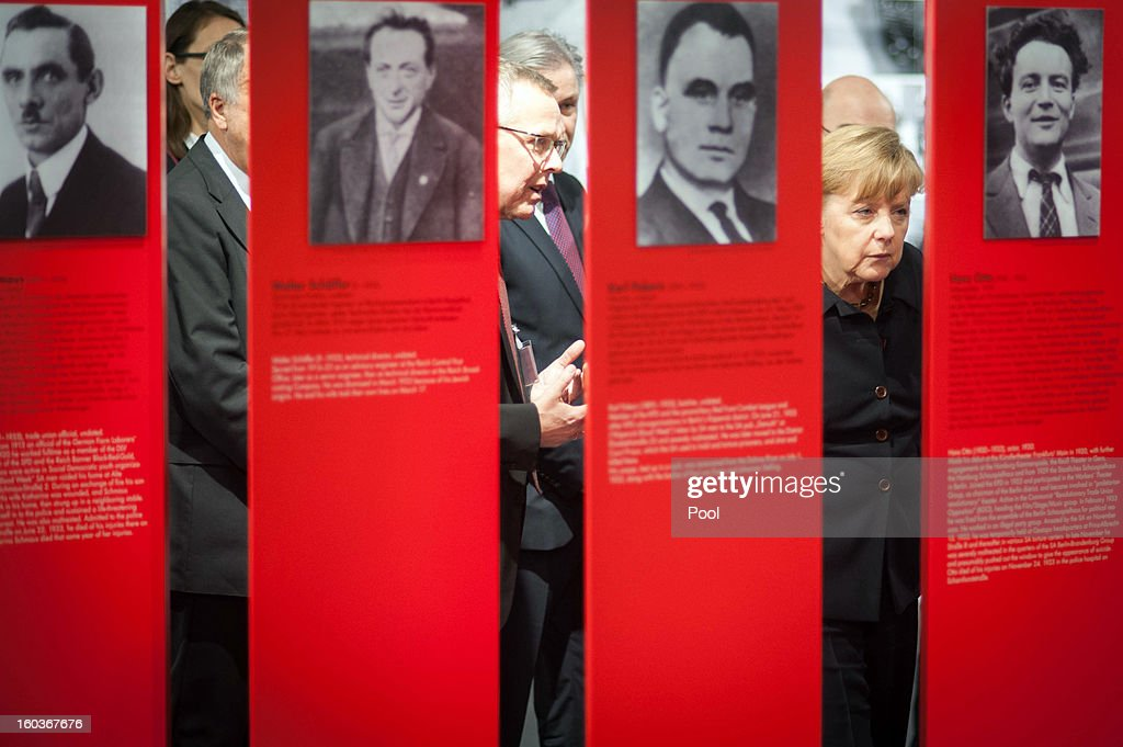 Chancellor Angela Merkel is seen viewing panels at the 'Berlin 1933 - Road to Dictatorship' exhibition at the Topography of Terror centre, which she will officially open today, on the former grounds of the SS headquarters on January 30, 2012 in Berlin, Germany.