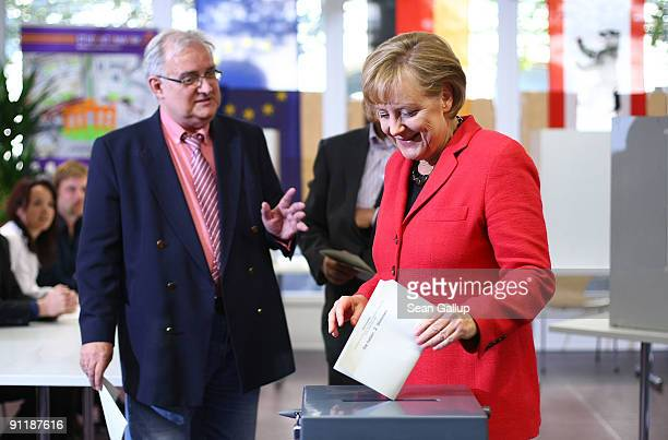 Chancellor Angela Merkel of the Christian Democratic Union party and her husband Joachim Sauer cast their ballots for German federal elections on...