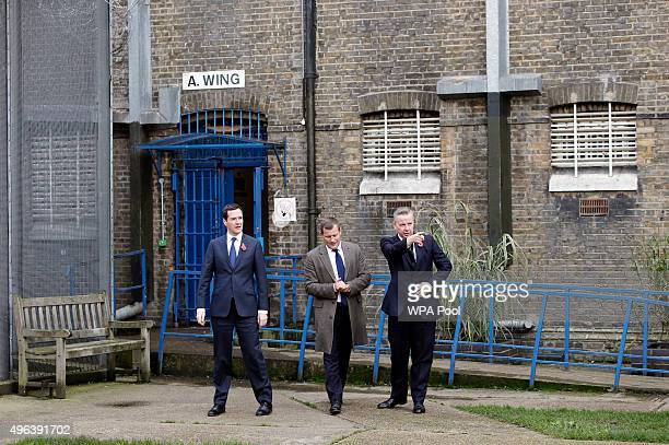 Chancellor George Osborne and Justice Secretary Michael Gove are given a tour by Prison Governor Giles Mason around the exercise yard outside A Wing...