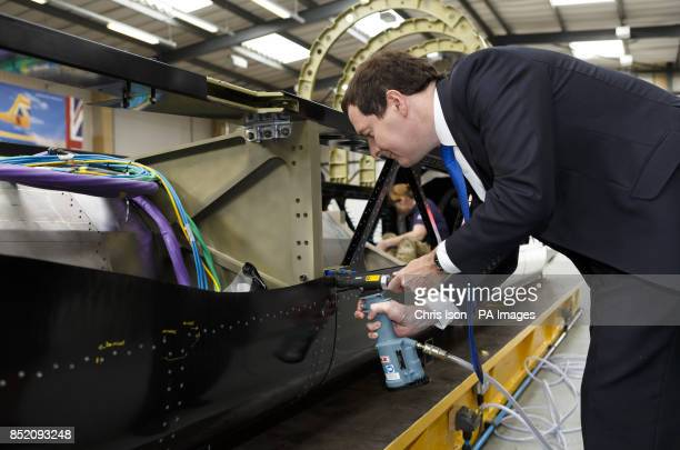 Chancellor George Osborne attaches rivets to land speed record car Bloodhound during a visit to the Bloodhound Technical Centre at Avonmouth near...