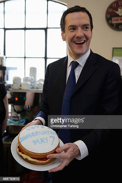 Chancellor George Osborne holds a cake declaring 'Vote Conservative May 7' during a visit to the Red Cone Cafe and visitor attraction on April 7 2015...