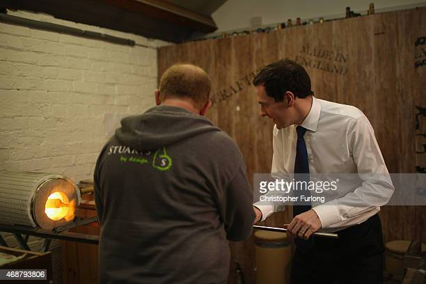 Chancellor George Osborne tries his hand at glass making under the watchful eye of glassmaker Stuart Caldicott during a visit to the Red Cone Cafe...
