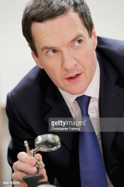 Chancellor George Osborne uses a magnigying glass to see clock parts in a clock repair shop during a visit to the Red Cone Cafe and visitor...